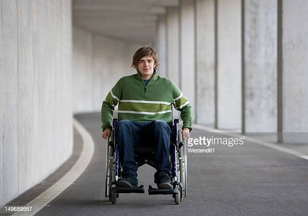 austria, mondsee, young man sitting on wheelchair at subway - wheelchair stock pictures, royalty-free photos & images