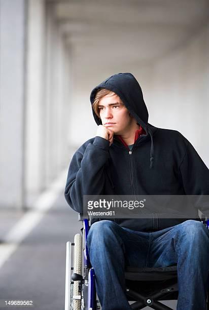 Austria, Mondsee, Young man sitting on wheelchair at subway