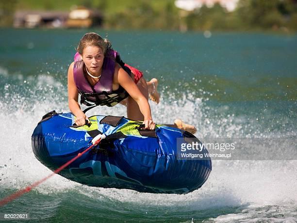 Austria, Moon Lake, teenage girl (16-17) riding water sled