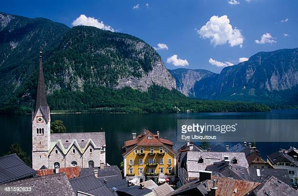 Austria Oberosterreich Hallstatt View over tiled village rooftops hotel and church with lake and mountains behind