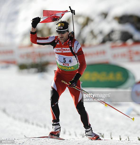 Austria s Christoph Sumann waves with an Austrian flag as he finishes the men's biathlon World Cup 4 x 7,5 km relay competition in Hochfilzen on...