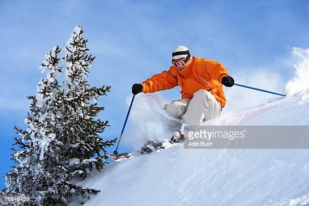 Austria, Saalbach, man skiing over ridge on slope
