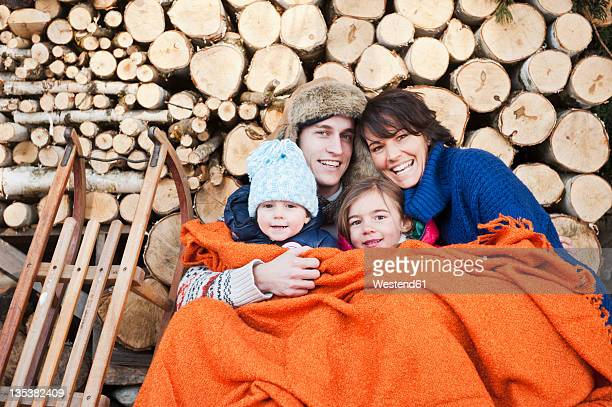 austria, salzburg country, flachau, family under woollen blanket sitting in front of firewoods - warme kleidung stock-fotos und bilder
