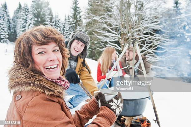 Austria, Salzburg Country, Flachau, Young men and women sitting near fireplace and making tea in snow