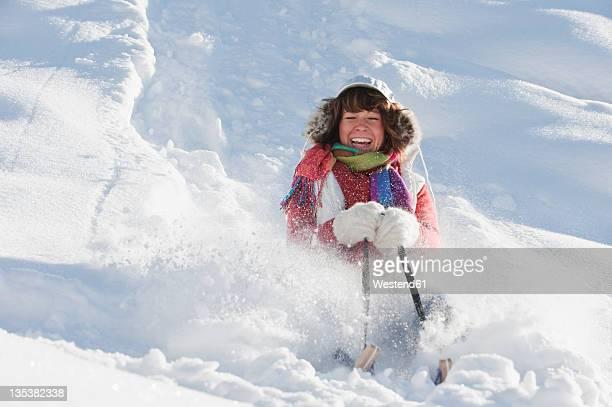 austria, salzburg country, flachau, young woman riding on sledge in snow - tobogganing ストックフォトと画像