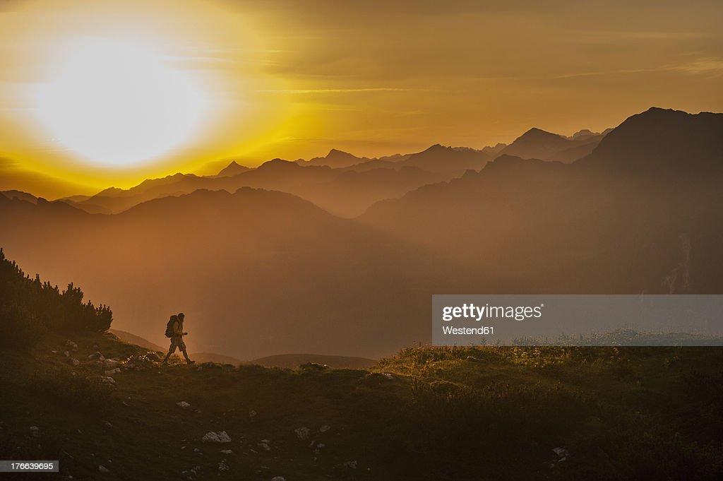 Austria, Salzburg Country, Man hiking through Niedere Tauern mountains at sunrise : Stock Photo