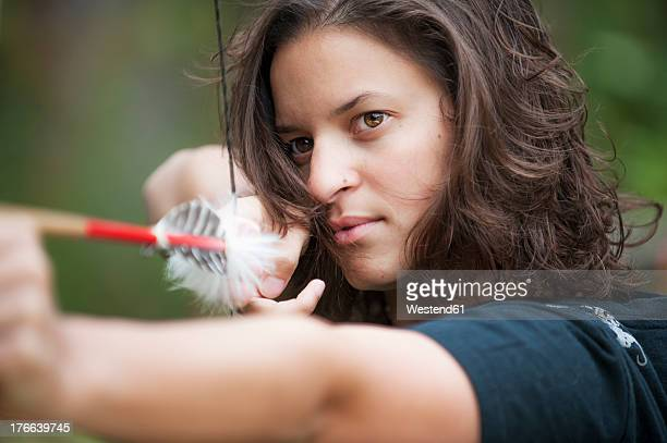 Austria, Salzburg Country, Young woman aiming arrow, close up