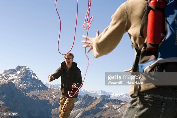 Austria, Salzburg County, Couple mountaineering, man throwing rope to woman