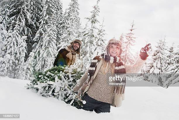 Austria, Salzburg County, Couple pulling christmas tree in winter landscape