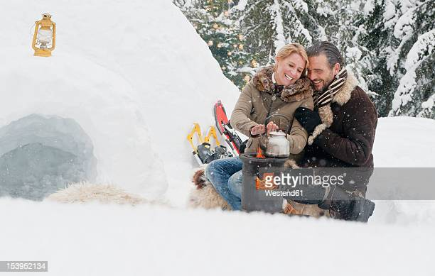 Austria, Salzburg County, Couple sitting near fireplace, smiling