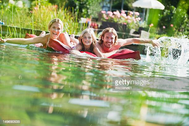 Austria, Salzburg County, Family on airbed in natural pool