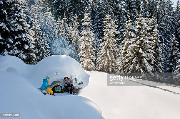 austria, salzburg county, family sitting near igloo - igloo stock pictures, royalty-free photos & images