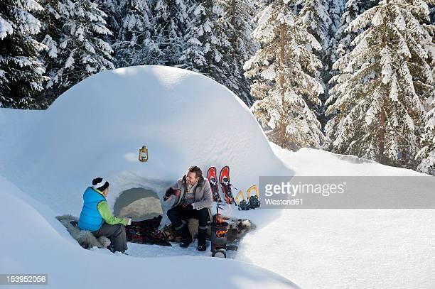 Austria, Salzburg County, Father and son sitting near igloo