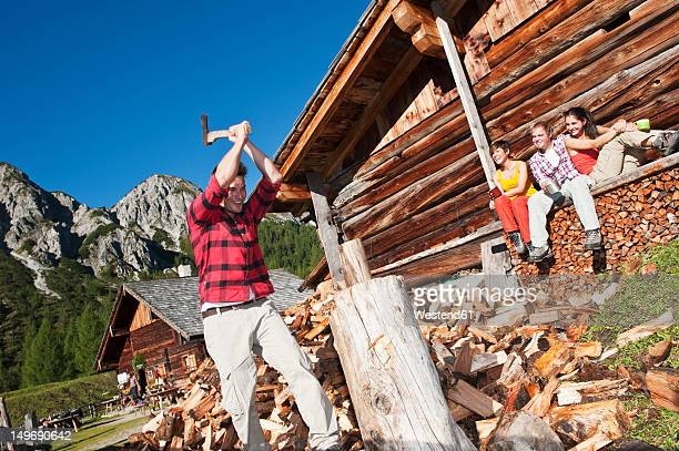 Austria, Salzburg County, Friends looking at man chopping wood near alpine hut