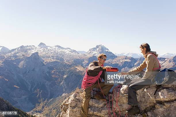 Austria, Salzburg County, Couple on mountain having drink, side view
