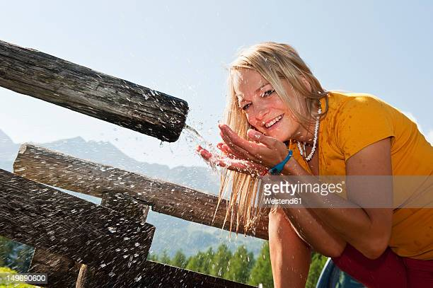 Austria, Salzburg County, Young woman drinking water from water trough, portrait