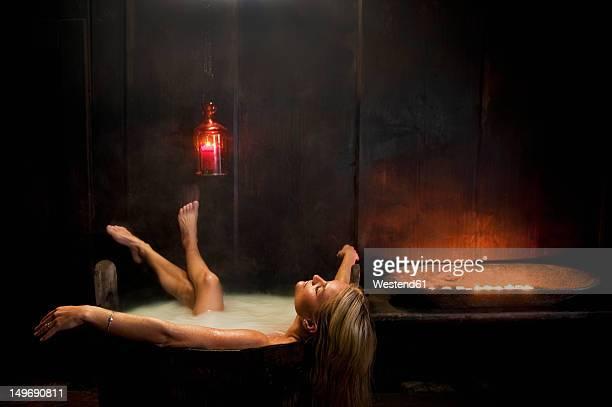 Austria, Salzburg County, Young woman taking bath in wooden tub