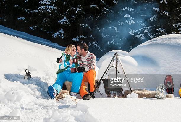 Austria, Salzburg, Couple preparing tea near igloo