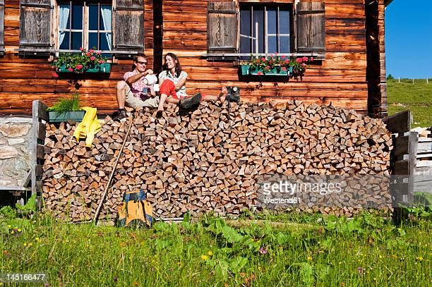 Austria, Salzburg, Couple sitting on logs by hut