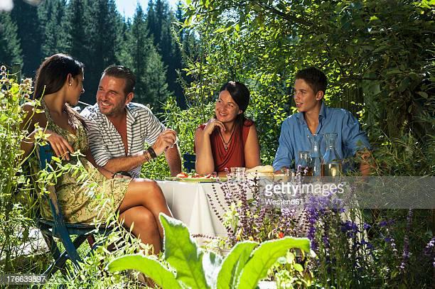 Austria, Salzburg, Family chating in garden