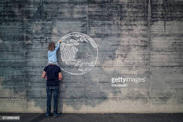 Austria, Salzburg, father with daughter in his shoulder, the daughter draw with chalk the earth on a concrete wall