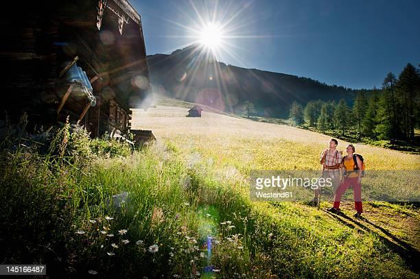 Austria, Salzburg, Filzmoos, Couple looking at alpine hut