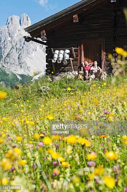 Austria, Salzburg, Filzmoos, Couple resting at alpine hut