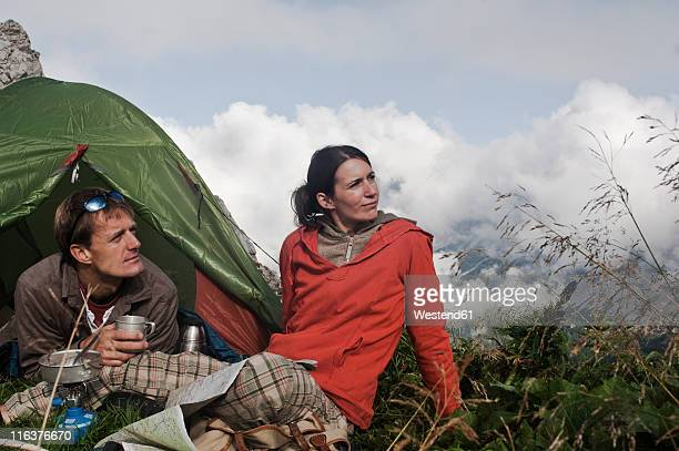 Austria, Salzburg, Filzmoos, Couple sitting beside tent on mountain and looking at view