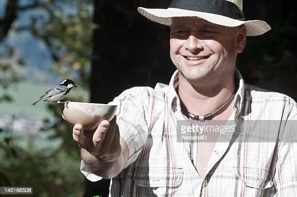 Austria, Salzburg, Flachau, Mature man feeding bird, smiling