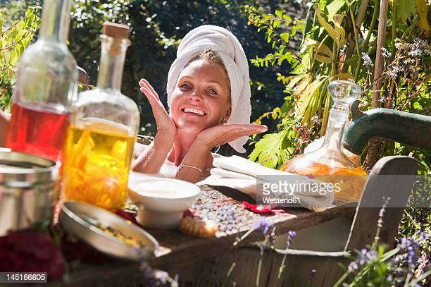 Austria, Salzburg, Flachau, Young woman taking milkbath in tun