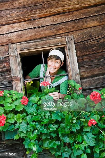 Austria, Salzburg, Flachau, Young woman watering flowers through window, smiling, portrait
