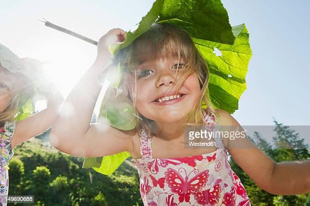Austria, Salzburg, Girls carrying leaf on head, smiling