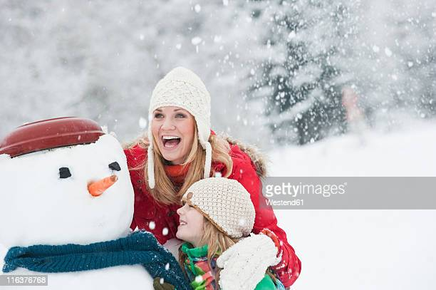 Austria, Salzburg, Httau, Mother and daughter with snowman, smiling