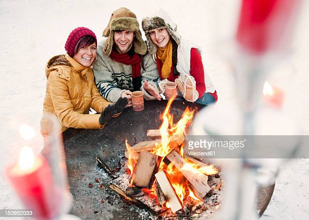 Austria, Salzburg, Man and women by fire at christmas market, smiling