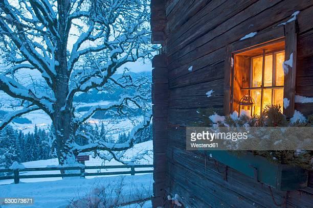 Austria, Salzburg State, Altenmarkt-Zauchensee, facade of wooden cabin with lightened window in winter