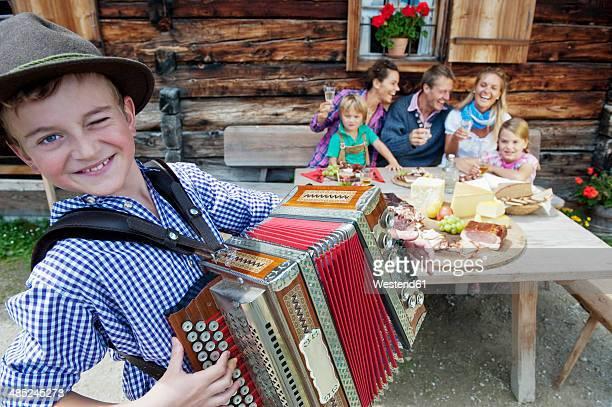 Austria, Salzburg State, Altenmarkt-Zauchensee, family having an alpine picnic while young boy playing accordion