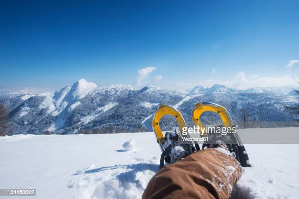 austria, salzburg state, altenmarkt-zauchensee, man with snowshoes lying in deep snow - lying in state stock pictures, royalty-free photos & images