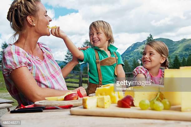 Austria, Salzburg State, Altenmarkt-Zauchensee, mother with two children having an alpine picnic