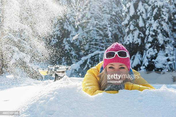 austria, salzburg state, altenmarkt-zauchensee, smiling young woman lying in snow, portrait - lying in state stock pictures, royalty-free photos & images