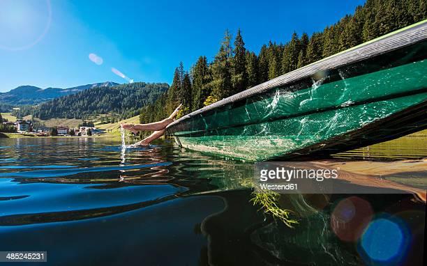 austria, salzburg state, altenmarkt-zauchensee, woman lying in a boat - österreich stock-fotos und bilder