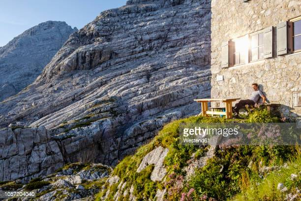 austria, salzburg state, loferer steinberge, hiker sitting at mountain hut enjoying the view - hut stock pictures, royalty-free photos & images