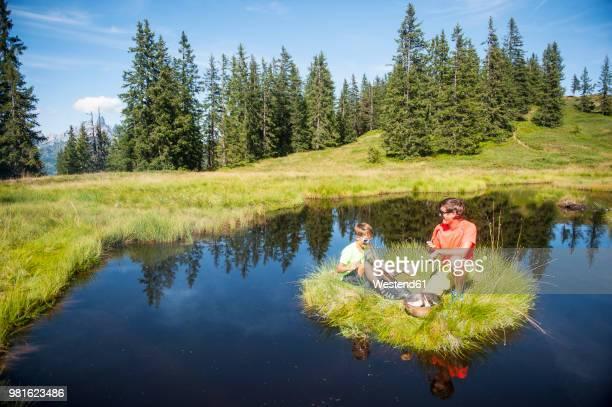 Austria, Salzburg State, Untertauern, father and son grilling on small island