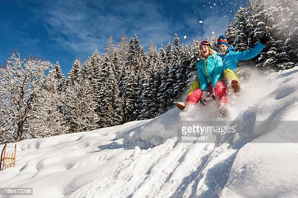 Austria, Salzburg, Young man and woman with sledge in snow at Altenmarkt Zauchensee