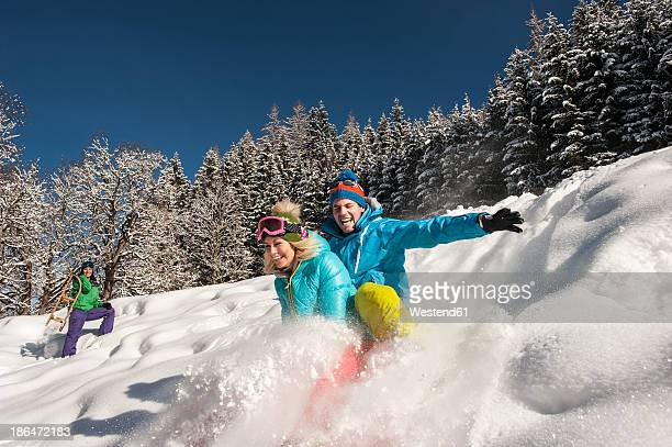 austria, salzburg, young man and women with sledge in snow at altenmarkt zauchensee - tobogganing stock pictures, royalty-free photos & images