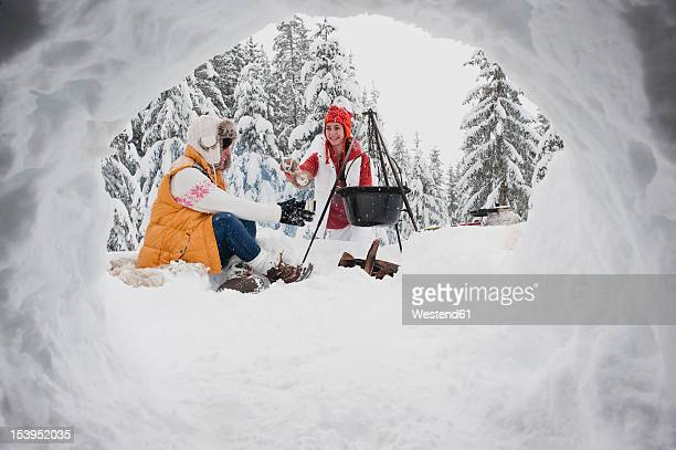 Austria, Salzburg, Young women sitting at fire place in winter
