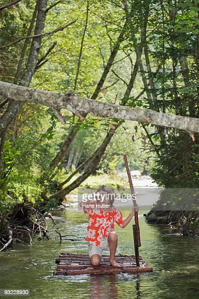 Austria, Salzburger Land, Boy (12-13) on wooden raft, shielding eyes