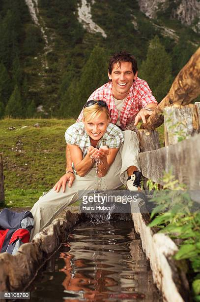 Austria, Salzburger Land, Couple drinking water from fountain, smiling, portrait