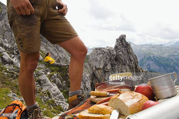 Austria, Salzburger Land, young couple having picnic on mountain, man standing on foreground