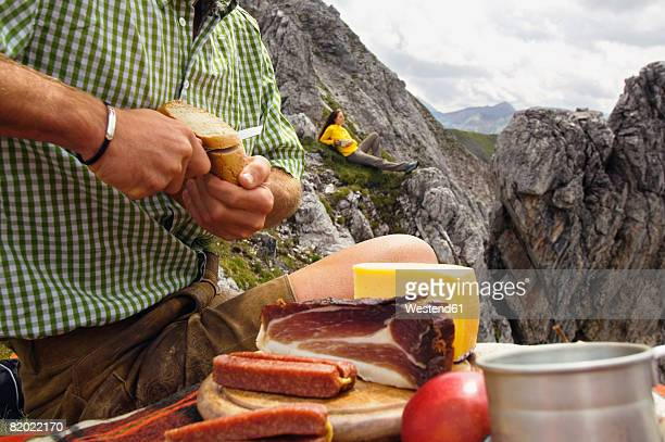 Austria, Salzburger Land, young couple having picnic on mountain, man cutting bread
