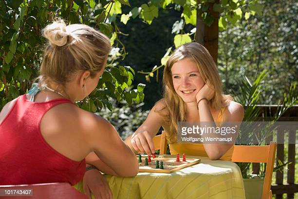 Austria, Salzburger Land, Teenage girls (14-15) playing ludo in garden